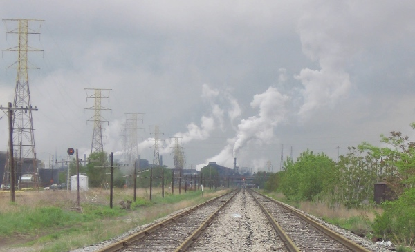 Railroad tracks lead toward a factory that is emitting smoke into the air.
