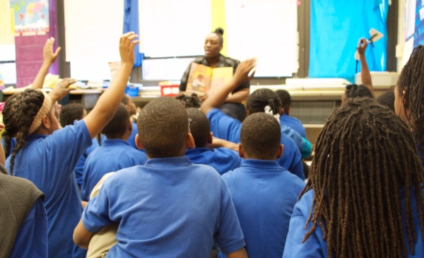A teacher reads a book and asks questions of students seated on the floor in front of her.