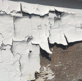 Paint peels away from a wall board.