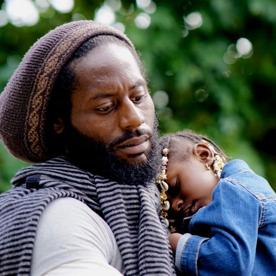 A Black father holds his sleeping daughter.