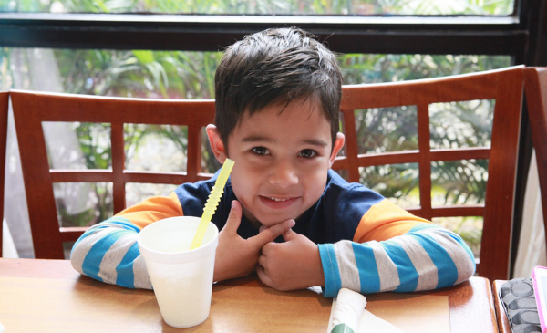 A child of Hispanic or Latino descent smiles while sitting at a table.
