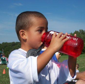 A child drinks water from a Nalgene bottle.