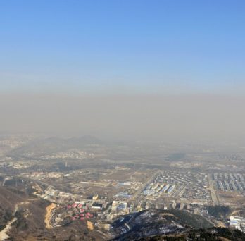 A view from a mountain of smoggy air covering an urban valley.