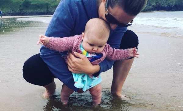 A mother holds up her infant daughter as she toddles along a beach.