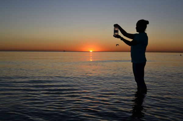 A person holds up a bottle of water from Lake Michigan that will be submitted for testing for chemicals and bacteria.